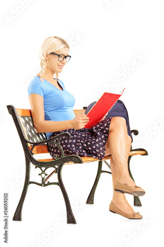Smiling blond female student sitting on a bench reading a book