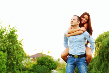 Happy woman jumped on man's back