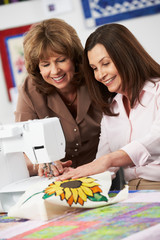 Two Women Using Electric Sewing Machine