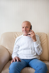 Smiling old man is talking on the phone