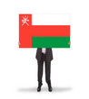 Businessman holding a big card, flag of Oman