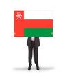 Businessman holding a big card, flag of Oman