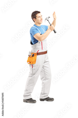 Full length portrait of a male manual worker working with hammer