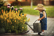 canvas print picture - cute little boy watering flowers watering can