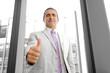Prospettiva di un uomo d'affari sorridente con pollice alzato