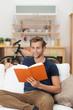 junger mann liest ein buch auf dem sofa