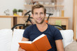 junger mann liest ein buch in seiner wohnung