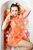 Beautiful sexy young woman in bath with flower petals