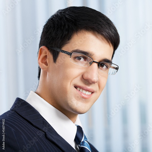 Happy smiling businessman at office