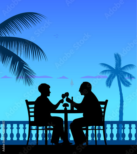 Lovely retired elderly couple drinking wine on the beach