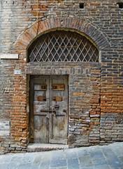 Antiqu door in Siena street. Siena, Italy