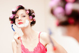 Beautiful funny girl shaving with foam & razor her face