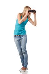 Full length blond woman looking through binoculars sideways