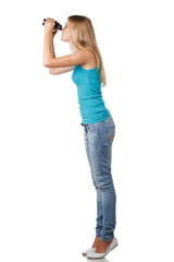 Side view of full length blond woman looking through binoculars