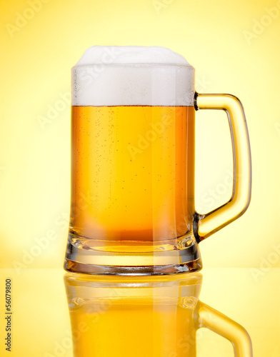 Mug fresh beer with cap of foam isolated over yellow background