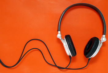 Headphones on orange background with copy space