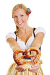 Happy woman in dirndl offering pretzel