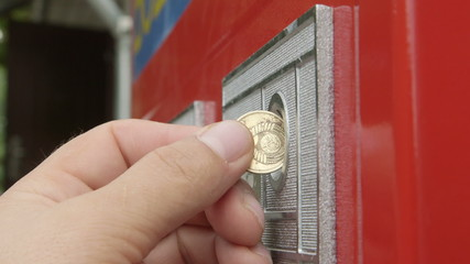Customer inserts coin into vending machine