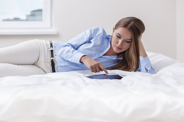 Beautiful woman using tablet computer on her bed