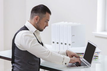 Young businessman using at laptop at desk