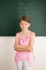 Schülerin löst Matheaufgaben an der Tafel