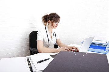 Young female doctor using laptop at desk in clinic