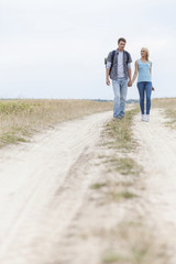 Full length of young hiking couple walking on trail at field