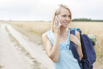 Young female hiker using mobile phone while standing on field