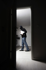 Side view of burglar stealing laptop from house