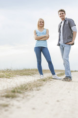Full length portrait of young couple standing on trail at field