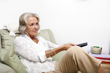 Senior woman using remote control while relaxing on armchair at home