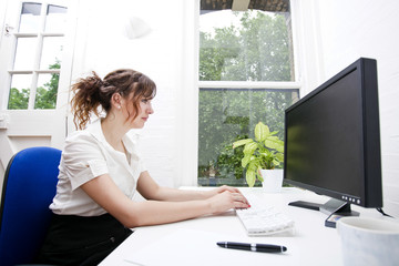 Side view of young businesswoman using computer at desk