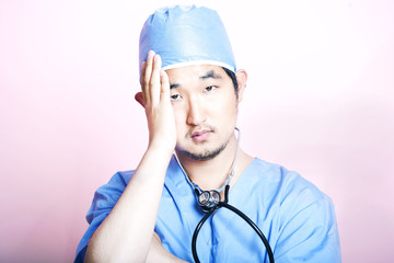 Young tired Asian surgeon wearing scrubs and looking stressed