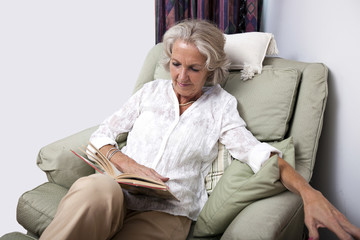 Senior woman reading book while relaxing on armchair at home