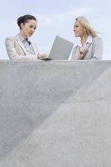 Low angle view of businesswoman using laptop while standing with coworker on terrace against sky