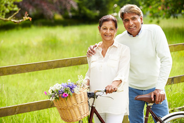 Senior Indian Couple On Cycle Ride In Countryside