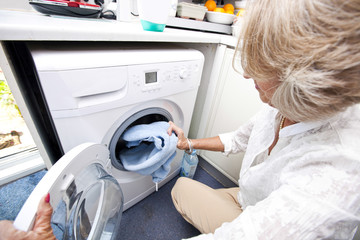 Senior woman loading towel in washing machine at home