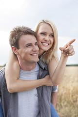 Happy woman showing something to man while enjoying piggyback ride at field