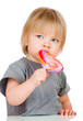 Baby eating a sticky lollipop