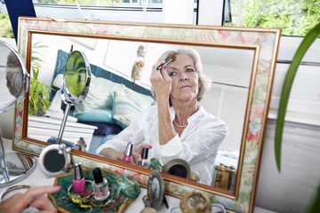 Mirror reflection of senior woman applying blusher at home
