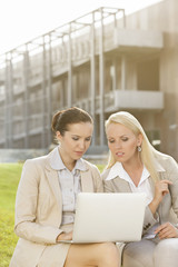 Young businesswomen using laptop together while sitting against office building