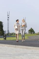 Full length of young businesswomen walking on street