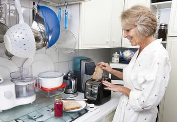 Happy senior woman preparing toast in domestic kitchen