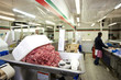 Minced meat in container with employee standing in background at store