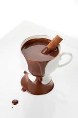 Hot chocolate with cinnamon stick on a white background
