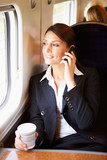 Female Commuter With Coffee On Train Using Mobile Phone