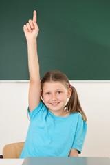 Fleißige Schülerin hebt Hand im Unterricht