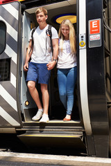 Young Couple Getting Off Train At Platform