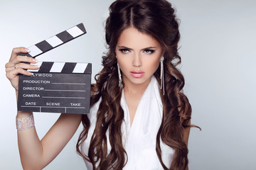 Beautiful brunette woman holding Clapper Board against a grey ba