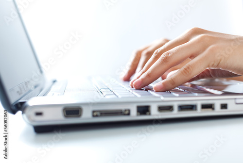 Hands typing on the laptop